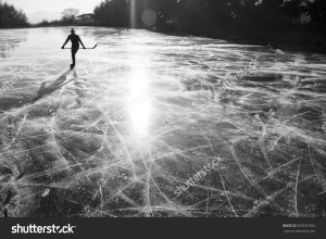 stock-photo-alone-hockey-player-on-frozen-ice-during-ice-skating-on-natural-ice-in-rural-environment-359561903